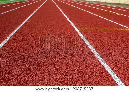 Track running. Red treadmill in sport field. Sports stadium in the open air