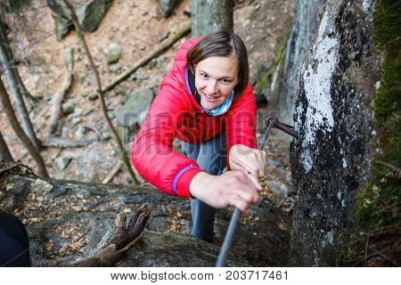 Woman climbing rock in the forest holding security railing ascending to the top succeeding. Active lifestyle progress and improvement conquering challenges concept.