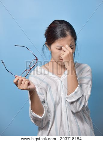 Tired Asian glasses woman rubbing eyes on blue background. Copy space. Overtime working.