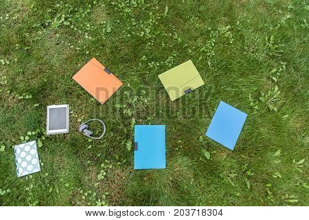Top view of colorful books, folders of documents, tablet, headphones and copybook on green grass