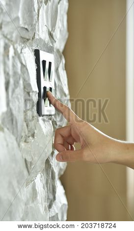 Close up hand turning on or off on grey or black lighting switch on rough stone wall. Copy space.