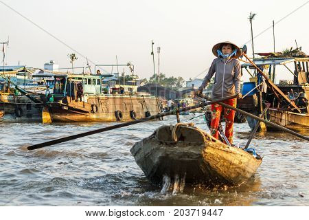 CAN THO VIETNAM - 3/24/2016: A merchant paddles through Cai Rang Floating Market on the Mekong river to sell products to tourists.