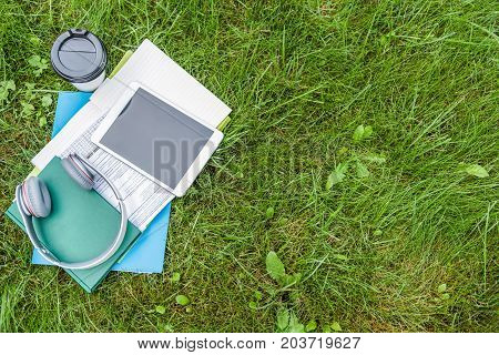 Top view close up of tablet, headphones on books and copybooks. Cup of coffee is near it on grass. Copy space in right side