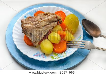 a hearty breakfast of chicken stewed carrot potatoes on a plate cupronickel cutlery