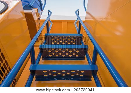 Some parts from a large yellow car for transportation of ore called Belaz black wheels blue stairs and others at the exhibition coal and mining