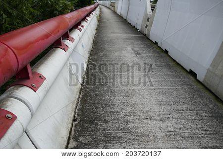 Sidewalk On A Bridge With Red Railing