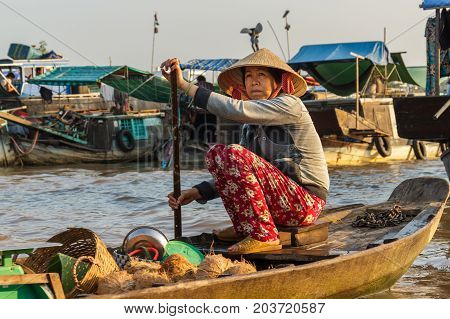 CAN THO VIETNAM - 3/24/2016: A coconut merchant paddles through Cai Rang Floating Market on the Mekong river to sell products to customers.