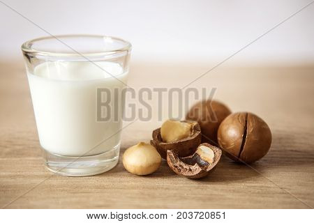 Close up macadamia nut milk on wooden table low fat healthy drink .