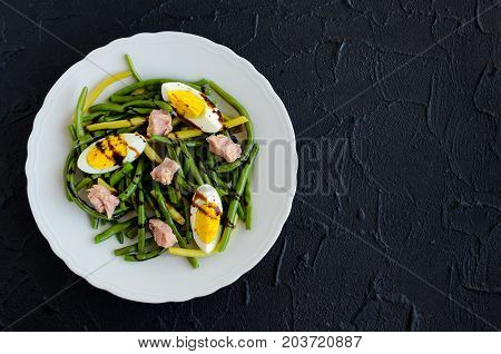 Summer warm salad with cooked green beans tuna boiled eggs and sauce balsamico glassa in white plate on black stone background with place for text. Healthy eating concept. Top view. Copy space.