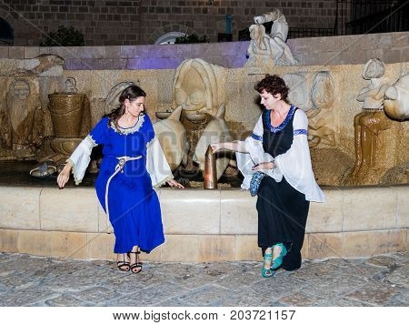 Tel Aviv-Yafo Israel September 08 2017: Two girls - members of the club of knights of Jerusalem dressed in traditional costumes of medieval ladies sit at night near the fountain in the old town of Yafo in Tel Aviv-Yafo Israel