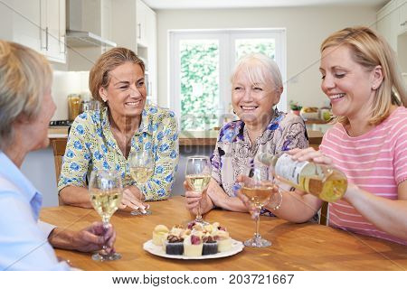 Group Of Different Aged Female Friends Relaxing At Home And Drinking Wine
