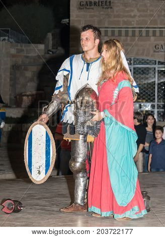 Tel Aviv-Yafo Israel September 08 2017: Members of the Knights of Jerusalem club dressed in traditional armor of a knight and a dress of ladies posing in front of photographers at night in the old town of Yafo in Tel Aviv-Yafo Israel