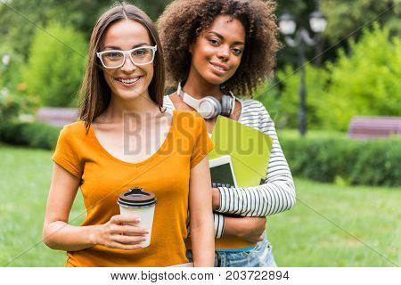 Waist up portrait of cheerful female friends standing in park and smiling. One woman is drinking coffee while her mulatto friend is carrying tablet with books