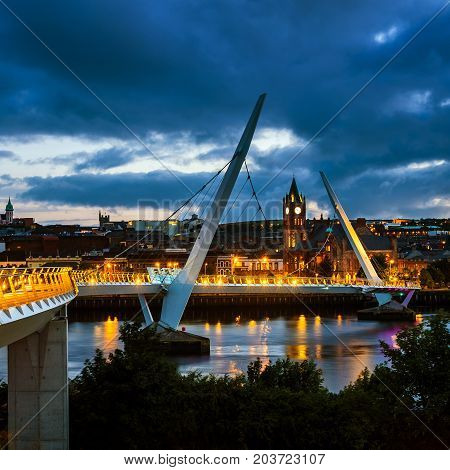 Derry Ireland. Illuminated Peace bridge in Derry Londonderry in Northern Ireland with city center at the background. Night cloudy sky reflection in the river.