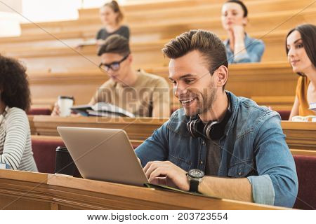 Portrait of carefree male student typing on laptop during interesting lecture. He is sitting at lecture hall near his group mates and smiling