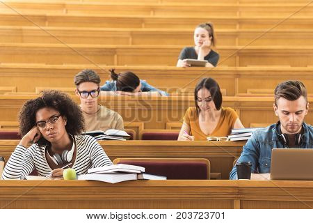 Boring lecture. Uninterested mulatto girl is sitting at lecture hall and making notes. Her group mates are doing their own business during lesson