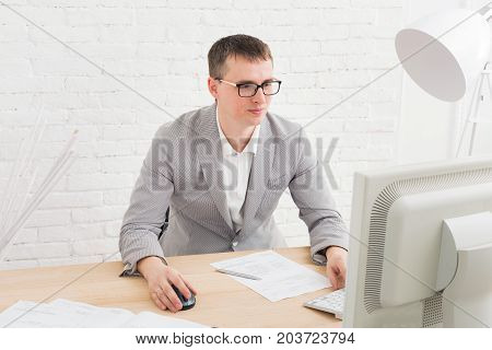 Young businessman working with laptop in modern white office interior. Handsome man in suit, successful employee at work with computer. Lifestyle portrait