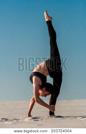 Young slim woman do gymnastic exercise at white sand beach under blue sky. Young gymnast on seashore