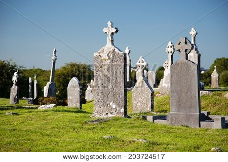 Ancient irish christian cemetery, tombstones standing in sunlight