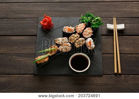 Japanese restaurant, gunkan sushi platter above view on rustic wood background and black slate plates.. Set with chopsticks, ginger, soy, wasabi.
