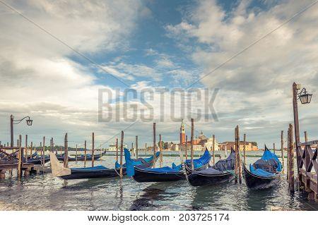 Pier with gondolas near Saint Mark`s Square in Venice, Italy. The gondola is a traditional romantic transport in Venice. San Giorgio Maggiore in the background.