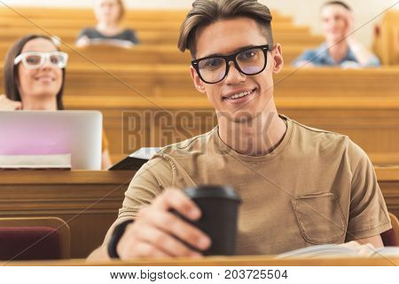 Waist up portrait of happy guy drinking coffee and smiling. He is sitting at table in auditory room at university