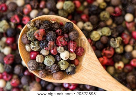 Close up mixed type of the peppercorns in wooden spoon on the peppercorns background