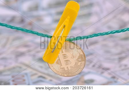 Money laundering concept. Yellow clothes peg hold Bitcoin.