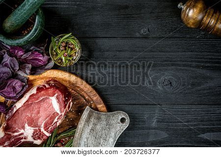 Fresh raw beef with spices, fresh basil and a sprig of rosemary with ax for meat on black wooden background. Top view. Copy space. Still life.. Dry Aged marble beef