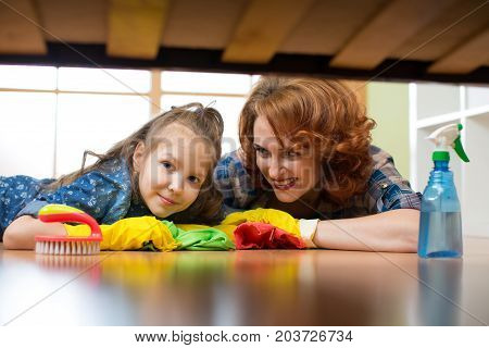 Family - mother and daughter do the cleaning in the house. Happy woman and little child girl wiped the floor.