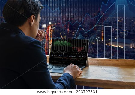 Businessman sitting and using computer laptop showing trading graph beside the windows glass over the Trading graph on the cityscape background Business financial concept, 3D illustration