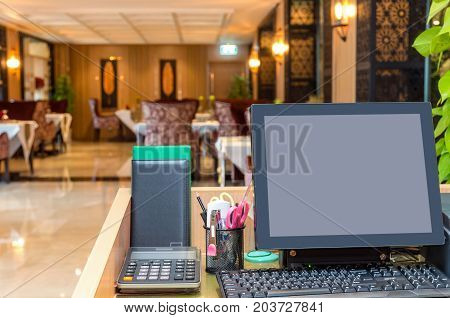 Cashier operating at the cash desk over the restaurant background business finance concept