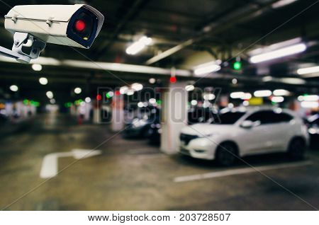 CCTV security indoor camera system operating with blurred image of under ground indoor car parking garage area RFID solution management system surveillance security and safety technology concept