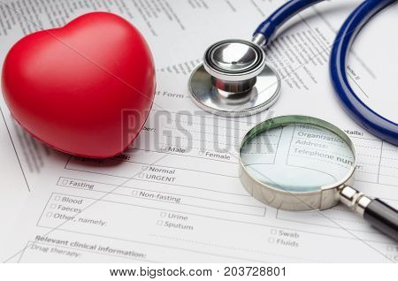 stethoscope red heart magnifying glass and patient information form on desk heart healthcare technology medical diagnosis heart disease medical report record history patient concept soft focus