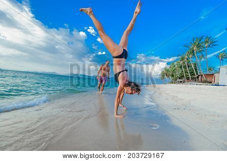Childhood In The Soul: A Couple Of Thirty-year-olds Jumping And Running Along The Tropical Beach, Fi