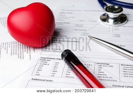 red heart pen stethoscope blood sample test tube patient information form on desk heart healthcare technology medical diagnosis heart disease medical report record and history patient concept