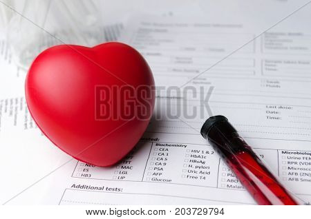 red heart test tube beaker and patient information form on desk heart healthcare technology medical diagnosis blood test medical report record and history patient concept selective focus