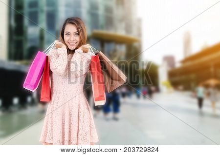 young asian woman beautiful smiling surprise and holding shopping bag while standing at outdoor department store shopping mall online payment shopping online lifestyle concept