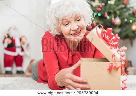 Pleasant gift. Joyful elegant old lady is lying on floor while opening Christmas present with curiosity