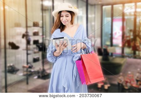 cheerful young asian woman watching special offer in tablet and holding shopping bag while standing at trendy new collection shoes store in department store shopping mall shopping online concept