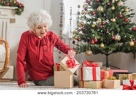 Happy celebration. Positive charming senior woman is sitting on floor among Christmas presents while opening decorated box with curiosity. Copy space in the right side