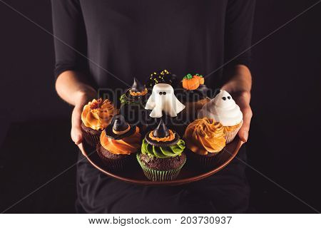 Person Holding Halloween Cupcakes