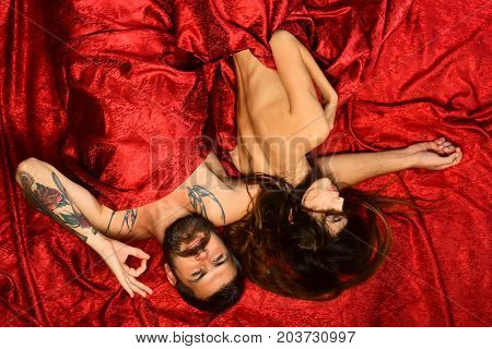 Couple In Love On Red Patterned Sheets. Man With Beard