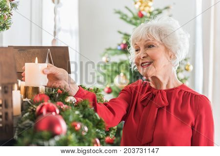 Magic of Christmas. Positive old woman is holding candle and expressing gladness. She is decorating her house with smile
