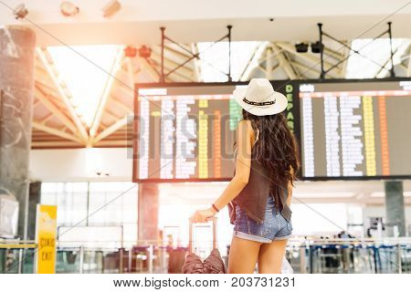 Young woman in international airport looking at the flight information board, checking her flight.Departures and arrivals board.Unrecognizable back