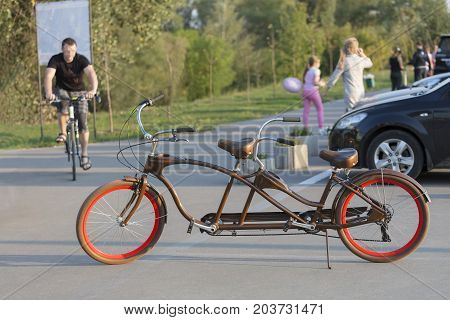 A chocolate-colored tandem bicycle with scarlet wheels is parked in a car park near the bike path in the evening sun.