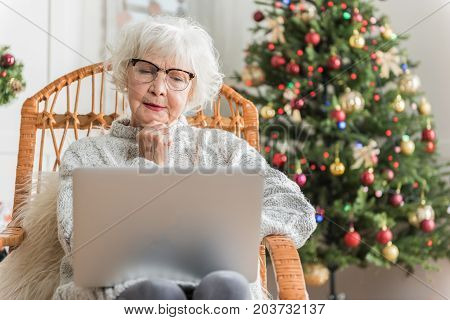 Bad news. Serious senior lady is sitting in chair and touching her chin while looking at screen of laptop and expressing sadness. Decorated Christmas tree on background. Copy space