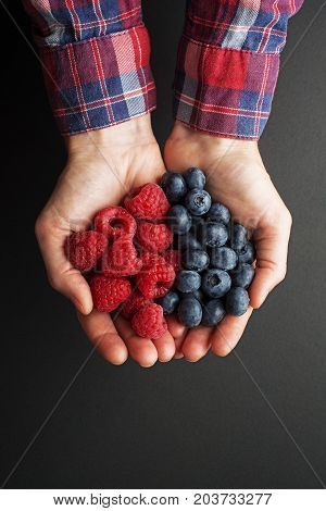 Woman hands holding fresh berries raspberries and blueberries on black background