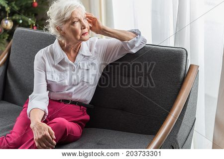 Feeling lonely. Thoughtful elderly lady is sitting on sofa and looking aside with sadness. She is leaning on elbow and touching her head. Copy space in the right side