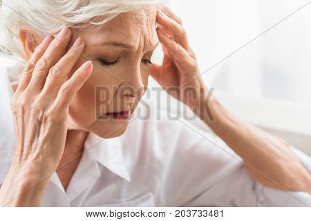 Awful headache. Close-up of face of old lady who is in great pain. She is touching her head and expressing suffering while sitting with closed eyes
